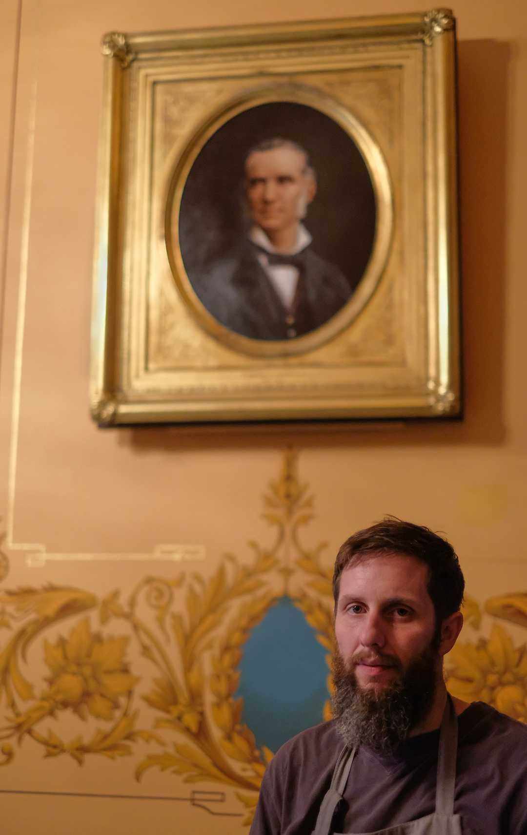 Joshua Risner below a portrait of Governer Charles Croswell