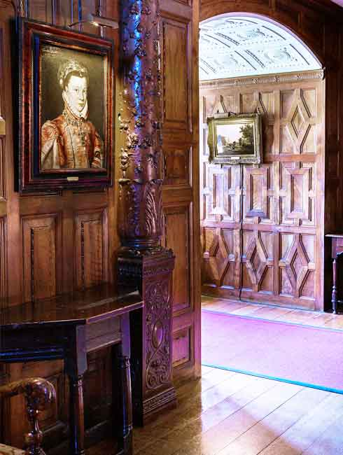 the carved inner hall of hever caslte with many hogarth classic picture lights